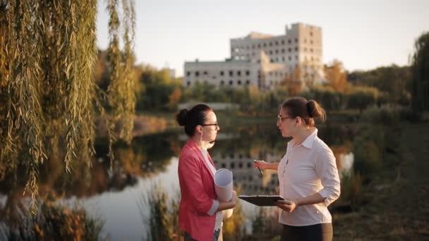 Dvě ženy jsou manažeři stavebních firem diskutovat o technické aspekty, stejně jako podněcování k odhadu dle technické dokumentace