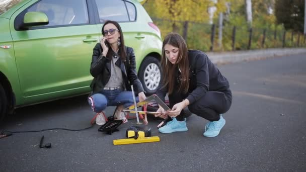 Two women call for help on the phone on the side of the road next to broken car