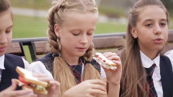Lányok főiskolai hallgató visel az azonos iskola egységes eszik szendvicseket, ül egy kerti padon, nevetve, és beszél