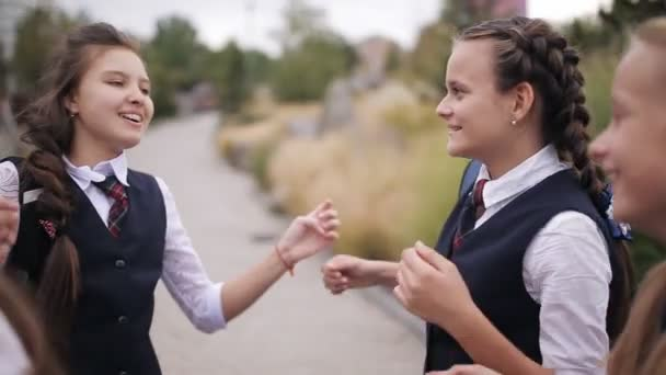 Schoolgirls having fun after school on the street. Girl student wearing the same school uniform laughing and singing after school in the Park.