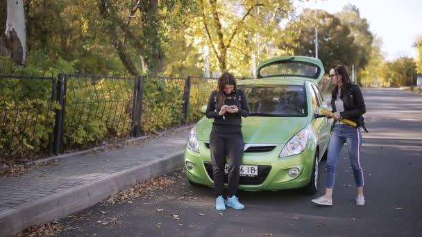 Két nő, egy zöld autó ütött a kereket, és telepítse a sürgősségi jele az úton.