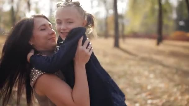Mladá matka se točí její dcera kolem sebe v podzimní městského parku. Šťastná rodina.