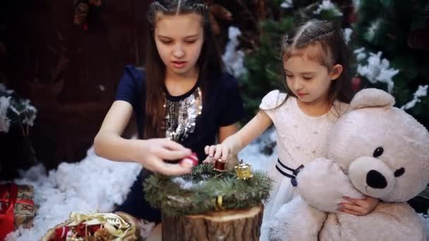 Zwei kleine Schwestern an einen Weihnachtsbaum vorbereiten ein Geschenk für die Großmutter. Glückliche Mädchen und Familie. Zwei kleine Mädchen an einen Weihnachtsbaum bereiten einen Weihnachtskranz als Geschenk für die Großmutter