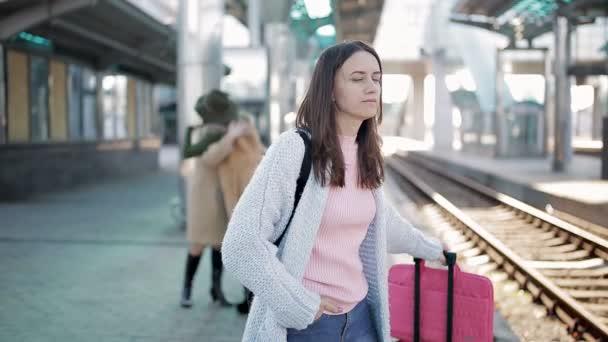 Mädchen warten Zug auf dem Bahnsteig am Bahnhof. Menschen verabschieden sich im Hintergrund