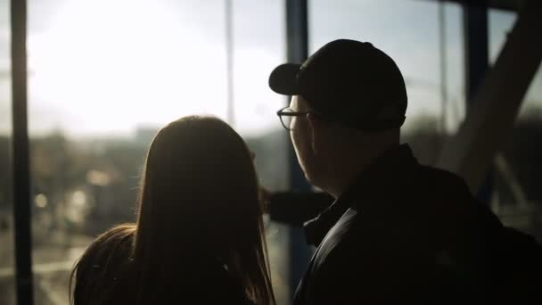 Silhouette of tourists at the airport. Boy and girl are standing in front of a window and talking cheerfully. Woman slaps the guy shoulder and laughs.