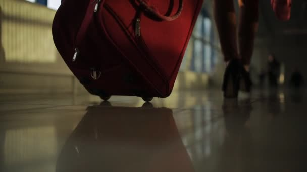 Close-up of the feet of passengers pass through the corridor of the airport and wheeling suitcases.