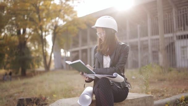 Architekt student ženu na staveništi prověří technickou dokumentaci a napíše do svého zápisníku