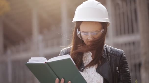 The woman student architect on a construction site examines the technical documentation and makes notes in his notebook