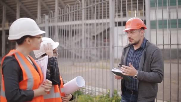 Ingenieurin kommuniziert und demonstriert die Baustelle der beiden Prüferinnen.
