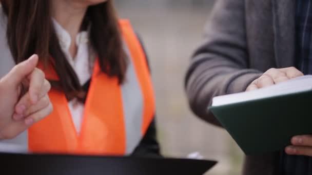 Ingenieurin kommuniziert und demonstriert die Baustelle der beiden Inspektorinnen aus nächster Nähe