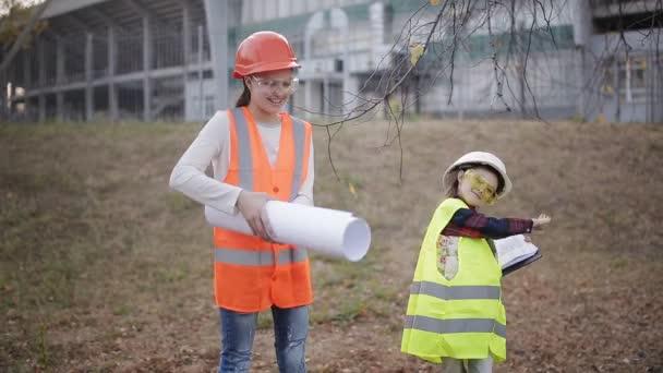 Dvě děti dívky v konstrukci helmy při pohledu na bílý list papíru nebo kreslení a usmívá se