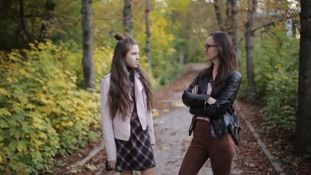 Mother and daughter talking in autumn Park.