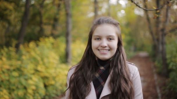 Nahaufnahme Porträt der schönen Teenie-Mädchen. Mädchen mit Zahnspange lächelt im Herbstpark in die Kamera