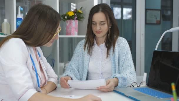 Rücksprache mit einem Arzt. die Frau am Empfang beim Arzt spricht über seine Beschwerden.