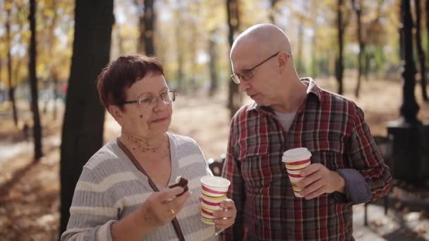 Starší pár podzim Park, mluví a pití kávy nebo čaje v plastových kelímků