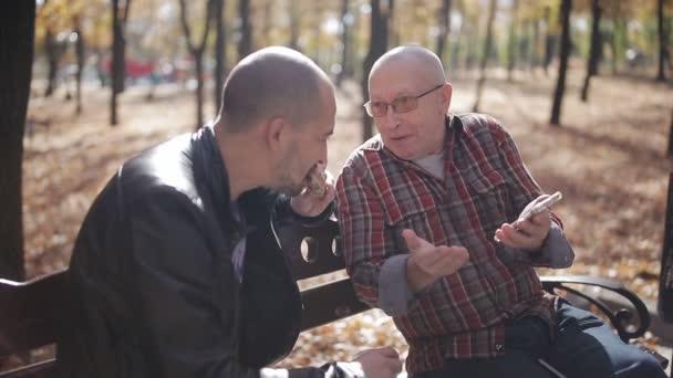 Ein älterer Vater und sein erwachsener Sohn sitzen auf einer Parkbank, trinken Kaffee und unterhalten sich. Erwachsener Sohn eines betagten Vaters bringt Smartphone im Herbstpark auf einer Bank bei.