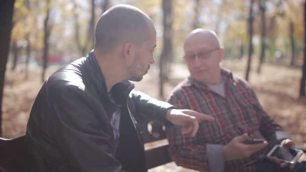 alter Vater mit erwachsenem Sohn im Park auf einer Bank, reden und trinken Kaffee. Erwachsener Sohn eines betagten Vaters bringt Smartphone im Herbstpark auf einer Bank bei.