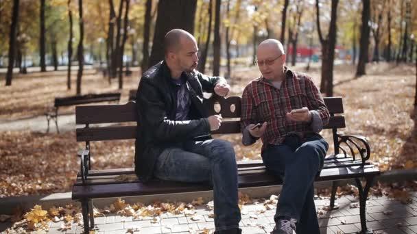 Erwachsener Sohn eines betagten Vaters bringt Smartphone im Herbstpark auf einer Bank bei.