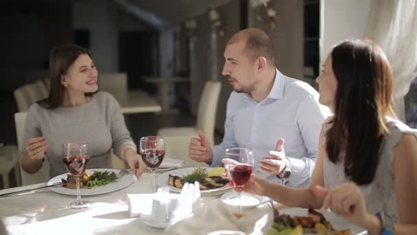 Muž ve společnosti dvou okouzlujících dam v restauraci nabízí sklenici s červeným vínem pro schůzky.