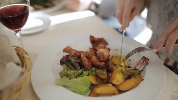 Detail dívky v restauraci jíst vidličkou a nožem. Žena na obědě v restauraci.