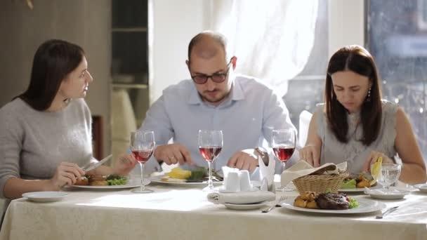 Přestávka na oběd v restauraci ve společnosti nejlepších přátel. Muž a dvě ženy v restauraci na oběd a pití vína.