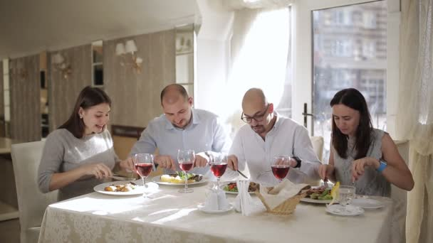 Four friends in the restaurant, eat meat and drink red wine in the glass.