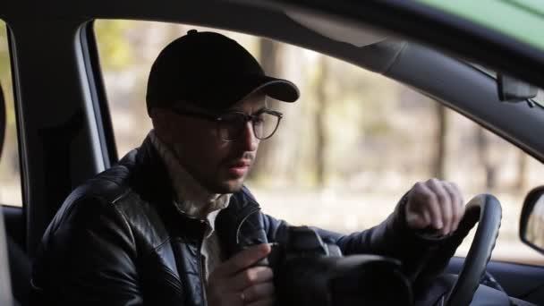 Spion, Paparazzi oder Detektiv im Auto, vor laufender Kamera.