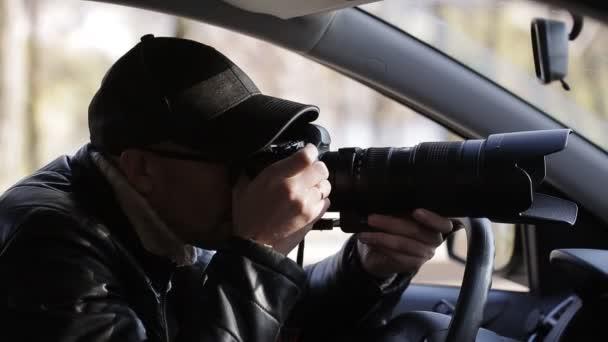 Privatdetektiv sitzt im Auto und fotografiert mit DSLR-Kamera