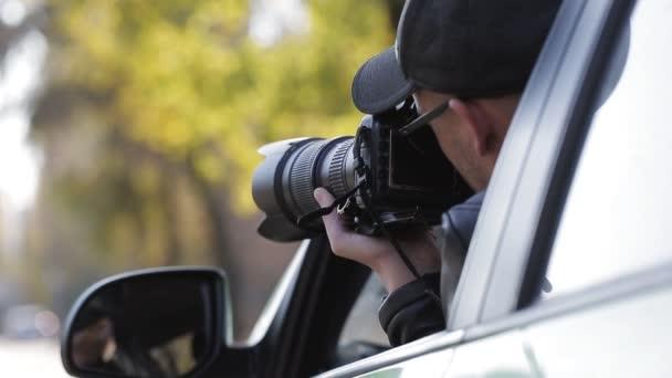 Spiegelung im Seitenspiegel eines jungen Privatdetektivs, der im Auto sitzt und mit DSLR-Kamera fotografiert