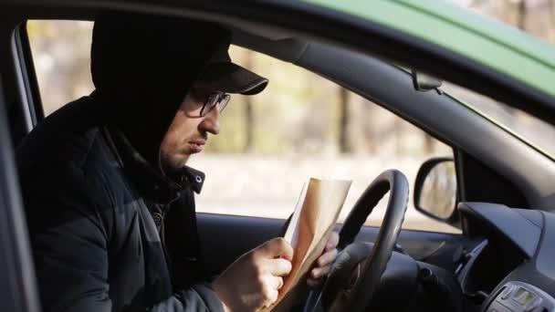 junger Privatdetektiv sitzt im Auto und fotografiert mit DSLR-Kamera