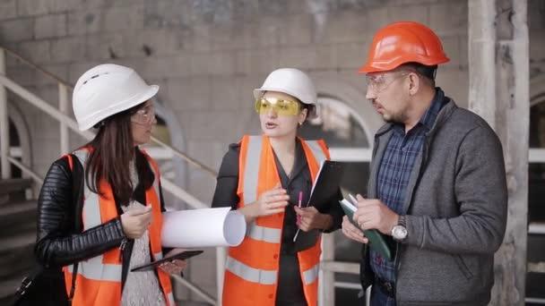 Inženýr komunikuje se zástupci ženské oddělení na staveniště, kontrola výkresů s skutečný průběh stavebních prací