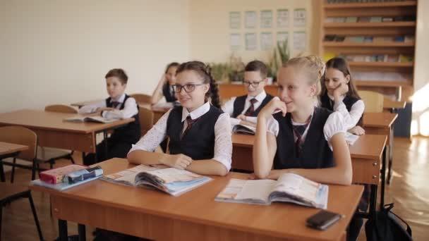 Studenti sedět u přepážek v učebně a poslouchat se zájmem poslouchat učitele