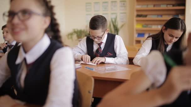 középiskolás diákok iskolai egyenruhát ül a tanteremben komnate. Vredny diák tesz egy papírrepülő során a leckét.