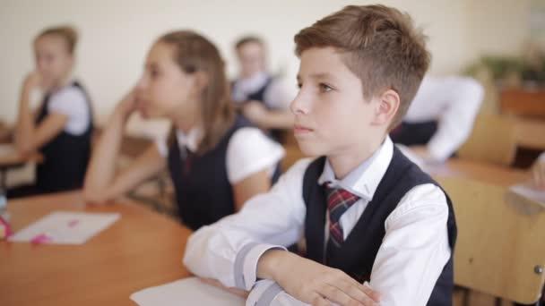 Proces učení. Studenti ve škole sedí ve svých křeslech naslouchat a odpovědět na otázky učitele.