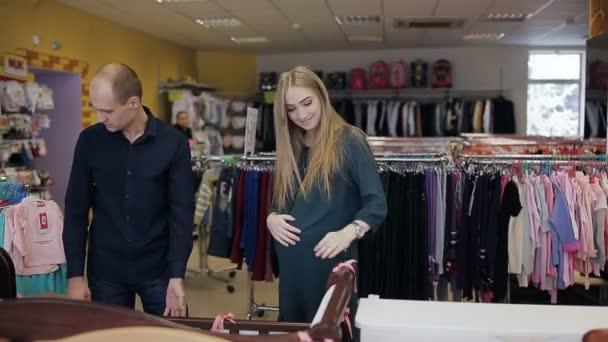 těhotná žena se svým manželem vybrat přebalovací stůl a dětská postýlka pro novorozence