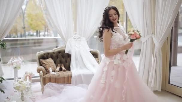 Mladá dívka v krásné růžové šaty na velkém a jasném pokoji, existuje mnoho svíček a jemný dekor. Šťastná nevěsta ve svatebních šatech smršť v tanci s její svatební kytice