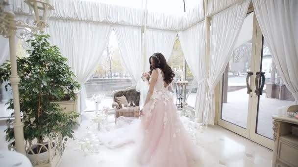 Egy fiatal lány, egy gyönyörű rózsaszín ruha egy tágas és világos szoba, van egy csomó gyertyák és a finom dekoráció. A boldog menyasszony, menyasszonyi ruha whirls a tánc az ő esküvői csokor