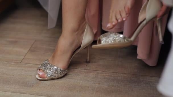 Elegantní bosá dívka nosí krásné boty s kamínky. Nevěsta na sobě svatební svatební boty sedí na posteli