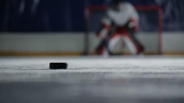 Hokejový brankář drží puk do branky nepřítele a způsobí drtivý úder.