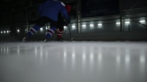 Dva hokejisté na kluzišti pro puk. Konfrontací na hokej mezi odpůrci.