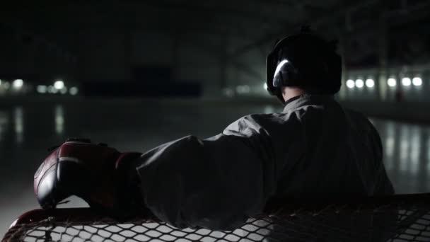 Brankář hokejový brankář stojí na bránu a sledování hráč na hřišti