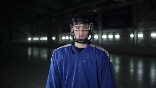 Pěkný hokejista. Usmála se na kameru na temná aréna, zblízka portrétní obránce, nebo vpřed kanadské hráče