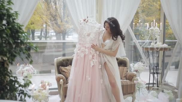 Boldog menyasszony a peignoir, megcsodálta a szépségét, esküvői ruháját