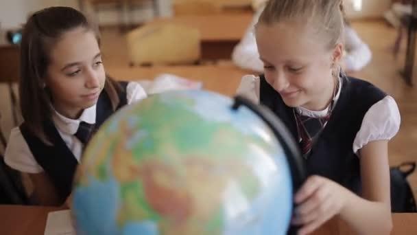 Školačka v třídě geografie studuje země a kontinenty se zeměkoule.