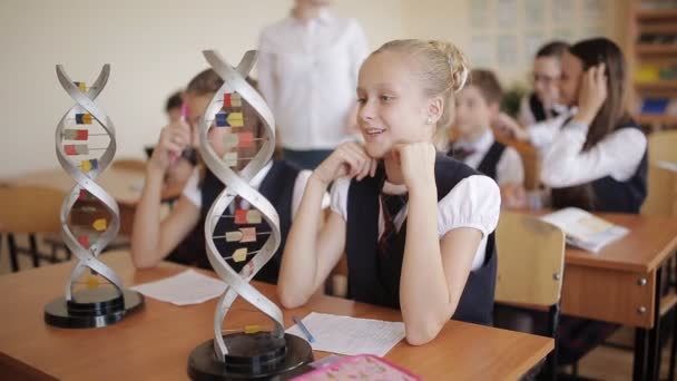 schoolchildren in school uniform are studying the layout of dna sitting in the classroom. The concept of school education.