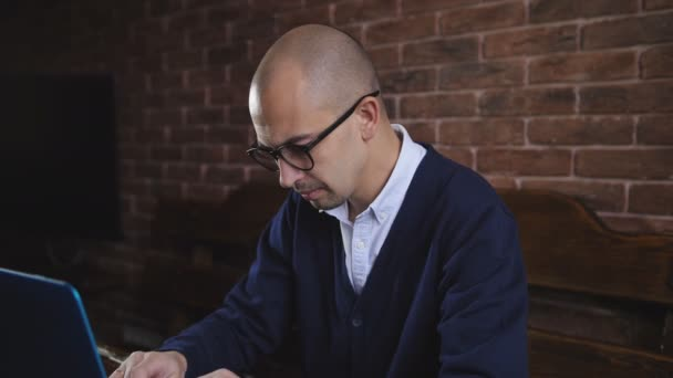 Pohledný muž střední-věku sedí u stolu v kanceláři a psaní na notebooku při práci na obchodního projektu