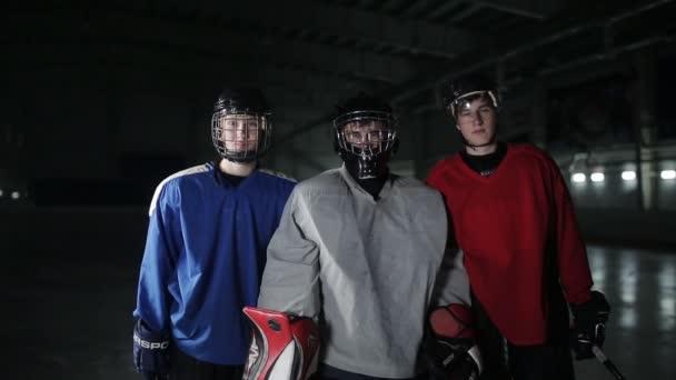 Portrét tří hokejistů. Brankář, útočník a obránce při pohledu na fotoaparát.