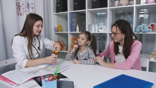 Reception, examination by a pediatrician at the medical clinic. The doctor opens a jar of vitamins and offers the girl.