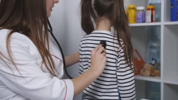 Ärztin wird ein Stethoskop verwendet, um das niedliche kleine Mädchen im Krankenhaus untersuchen. in Zeitlupe.