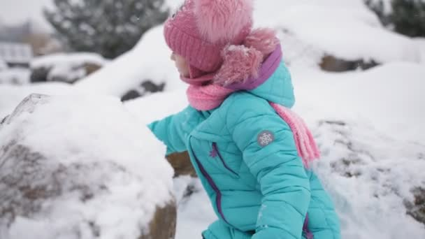 Little girl playing in the snow in the winter. Little girl prepares small snowballs for snowball battles with the help of special devices.
